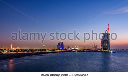 Sunset in Jumeirah, with on the left the Jumeirah Hotel, the Burj Al Arab and in the background the Marina of Dubai - Stock Photo