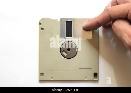 Detail of floppy disc on a white isolated background. A hand moves the retractable metal sleeve, that covers a window - Stock Photo