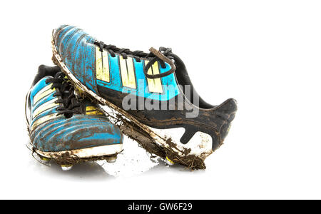 Muddy Football Boots on a white background - Stock Photo