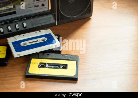 Vintage cassette tapes with radio-cassette player on a wooden table. - Stock Photo
