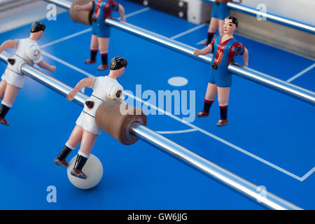 Detail of table football players, painted white, red and blue stripes playing against each other. - Stock Photo