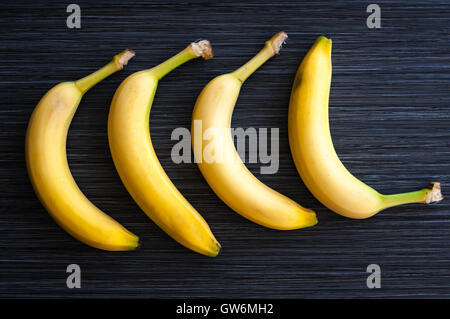 four ripe bananas laid out in a row on dark background close-up - Stock Photo