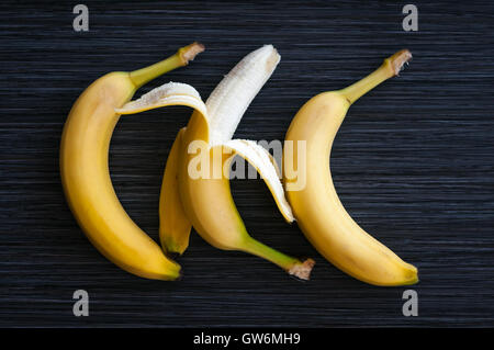 three ripe bananas are laid out in a number of average opened the half on a dark background - Stock Photo