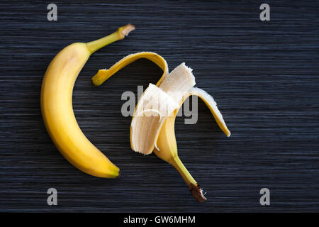 two ripe bananas laid out in a row one opened the half on a dark background - Stock Photo