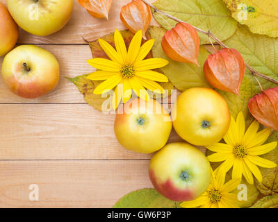 Apples, yellow flowers, physalis lanterns and autumn leaves on the wooden planks background - Stock Photo