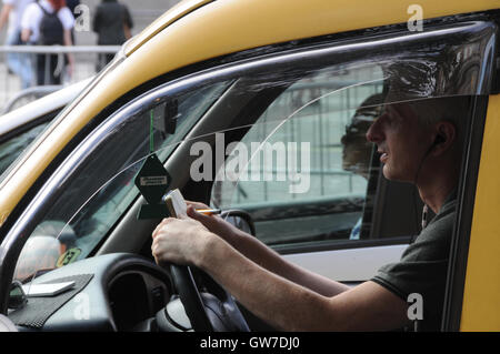 A London Taxi driver finds time to multi-task, whilst stuck in traffic. - Stock Photo