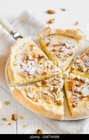 Homemade pastry - pie with nuts, seeds and mascarpone cheese on white background close up - Stock Photo