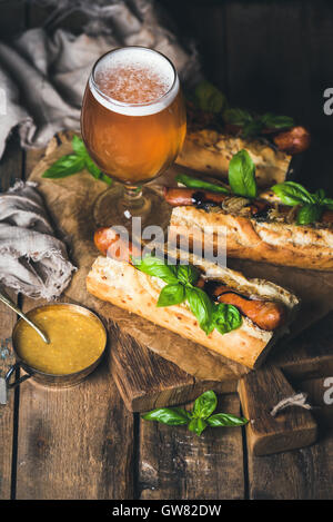 Glass of wheat beer and grilled sausage dogs in baguette - Stock Photo