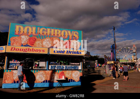 County fair midway with ferris wheel, rides and food stalls - Stock Photo
