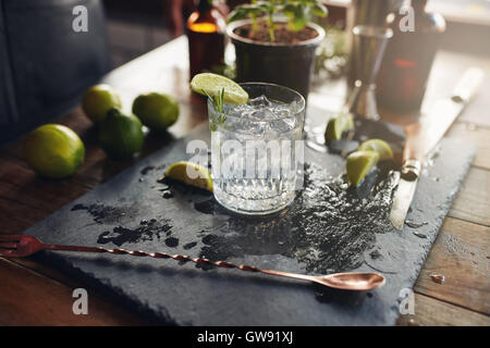 Close up of glass of a freshly prepared gin and tonic with lemon slices and spoon on the counter. - Stock Photo