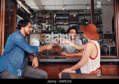 Young friends at cafe toasting drinks while sitting at a table. Three young people, two men and a woman meeting - Stock Photo
