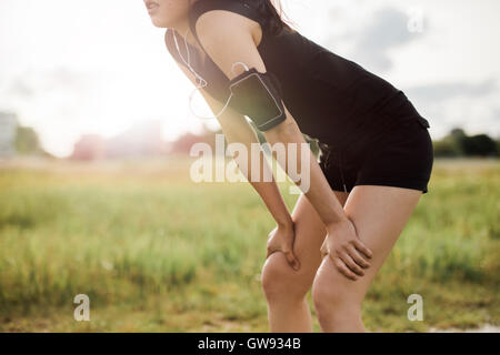 Young woman leaning over in sports gear. Determined sports woman looking forward for run. - Stock Photo