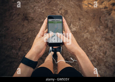 Woman checking the summary of her run on smartphone. POV shot of woman runner using a fitness app on her cellphone. - Stock Photo