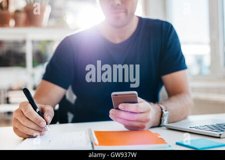 Businessman using mobile phone while writing in diary. Close up shot of man hands working at his desk. - Stock Photo