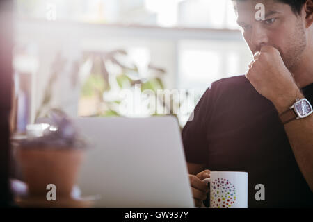 Serious male executive looking at laptop computer. Businessman sitting at his desk with cup of coffee in office. - Stock Photo