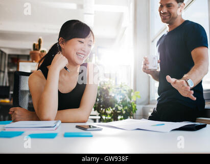 Shot of two young business partners discussing new ideas and smiling. Young people working together in office. - Stock Photo