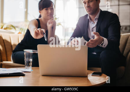 Shot of young woman presenting business idea on laptop to businessman. Executives meeting in a office lobby discussing - Stock Photo