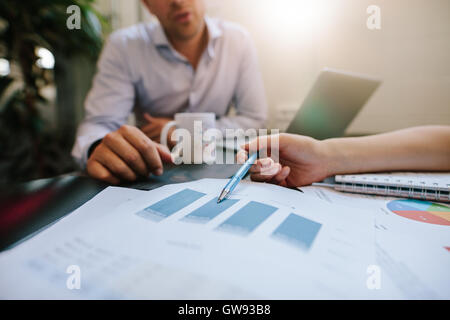 Close up shot of coworkers reviewing paperwork together in office. Businesspeople analyzing graphs during a meeting. - Stock Photo