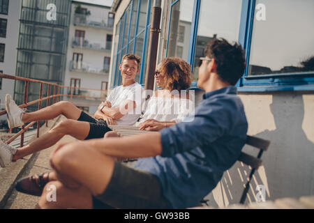 Three young friends at outdoor cafe. Multiracial group of young people relaxing outdoors at cafe table. - Stock Photo