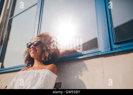 Outdoor shot of happy young african female sitting outdoors and smiling. Woman wearing sunglasses sitting outside - Stock Photo