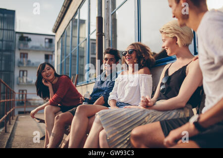 Multiracial group of friends sitting in balcony and smiling. Young people relaxing outdoors in terrace. - Stock Photo