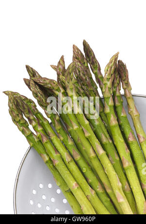 Organic Asparagus just washed in a white colander - Stock Photo