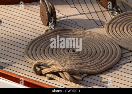 Coiled line and cleat on the deck of on 1938 classic sailing yacht 'Serenade' - Stock Photo