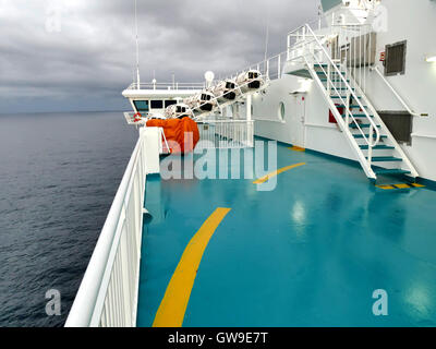 Inflatable life rafts in hard-shelled white containers and red lifebuoy hanging on railings. Modern passenger ship - Stock Photo