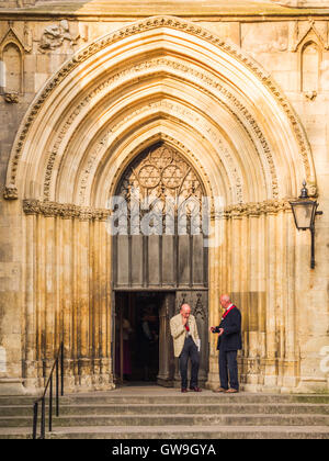 Two gentlemen converse at the west entrance to York Minster, one of the largest of its kind in Northern Europe. - Stock Photo