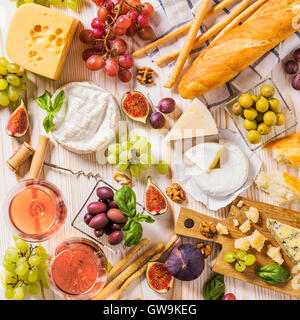 Assortment of cheeses, fruits, breads, wine and snacks on white - Stock Photo