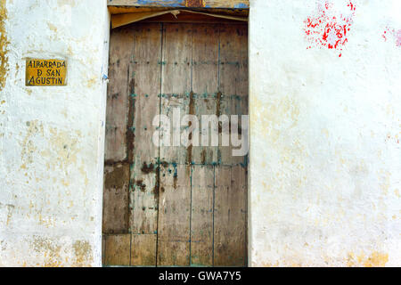 Rustic wooden door on a white historic building in Cartagena, Colombia - Stock Photo