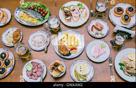 Food from above on a wooden table with young people around eating a variety of food - Stock Photo