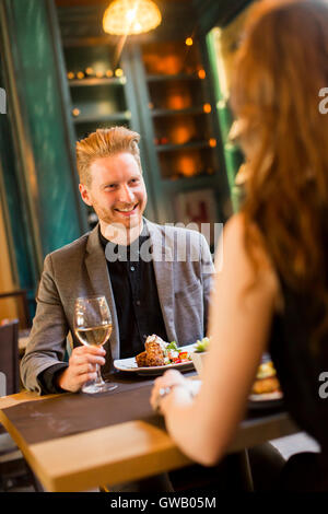 Handsome young redhair couple having dinner in the restaurant - Stock Photo