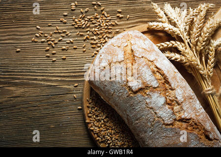 Homemade loaf of bread on wooden table - Stock Photo