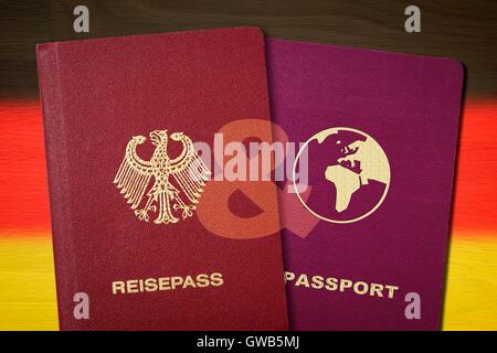 German and second passport before Germany flag, symbolic photo double citizenship, Deutscher und zweiter Pass vor - Stock Photo