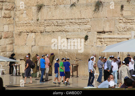 Young Jewish boys along with other worshipers praying at the mens side of the Western Wailing Wall which is also - Stock Photo