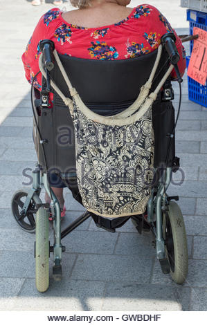 Close-up from behind of a woman sat, waiting,  in a wheelchair, Salisbury Market Place, Wiltshire, England - Stock Photo