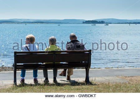 Two women and a man sitting on a bench looking over the harbour, Poole, Dorset, England - Stock Photo
