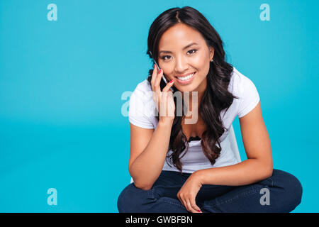 Portrait of a cheerful smiling asian woman talking on the phone while sitting on the floor isolated on a blue background - Stock Photo