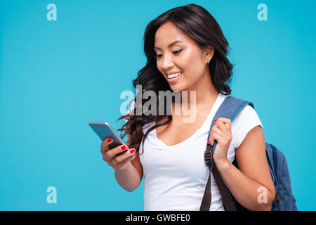 Cheerful young vietnamese girl with backpack using smartphone isolated on a blue background - Stock Photo