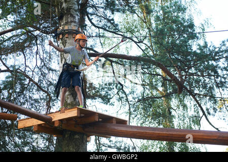 Portrait of active brave boy enjoying outbound climbing at adventure park on tree top - Stock Photo