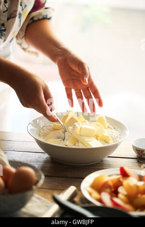 Woman miking butter and flour - Stock Photo