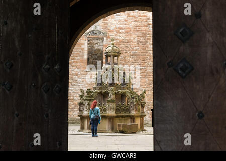 Linlithgow Palace James V restored fountain in the centre of the courtyard seen through the doors of the former - Stock Photo