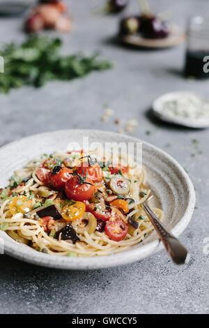 A bowl of eggplant pomodoro pasta is photographed from the front view. - Stock Photo