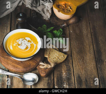 Pumpkin cream soup in bowl with basil leaves, spices and grilled bread slices served with fresh pumpkin over old - Stock Photo