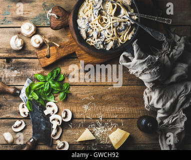 Italian style dinner with copy space. Creamy mushroom pasta spaghetti in cast iron pan with Parmesan cheese, fresh - Stock Photo
