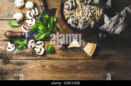Italian style dinner. Creamy mushroom pasta spaghetti in cast iron pan with Parmesan cheese, fresh basil and pepper - Stock Photo
