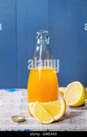 Opened glass bottle of citrus orange and lemon lemonade, standing with sliced fruits on stone board with blue background. - Stock Photo