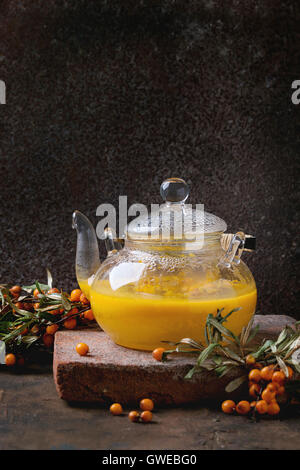 Hot berry sea buckthorn tea drink with apples in glass teapot on clay board, served with glass cup, saucer, fresh - Stock Photo