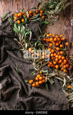 Ripe sea buckthorn berries on a branch with leaves on sackcloth rag over old wooden textured background. Top view - Stock Photo